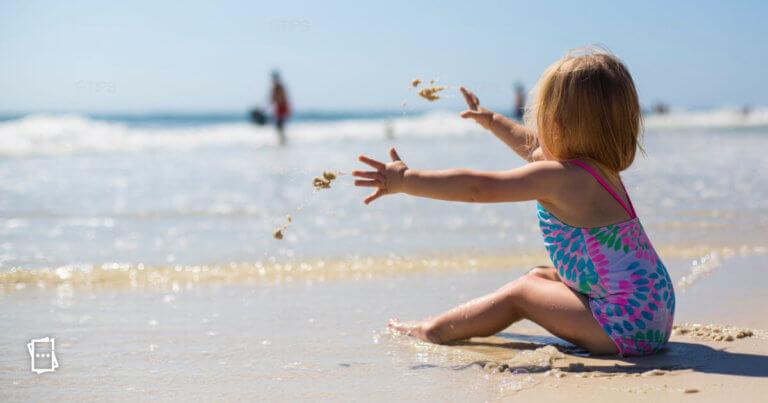 bimba con costume contenitivo che gioca in spiaggia